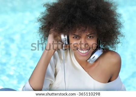 young black girl listening music at big headphones near pool during spring break. - stock photo