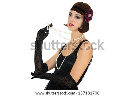 Young black hair girl with the flower in the hair dressed in  black dress and holding white pearls