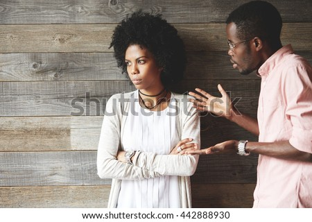 Young black indignant male gesticulating, arguing with his dark skinned girlfriend, who is standing against wooden wall with crossed arms, looking away with deeply offended expression on her face - stock photo
