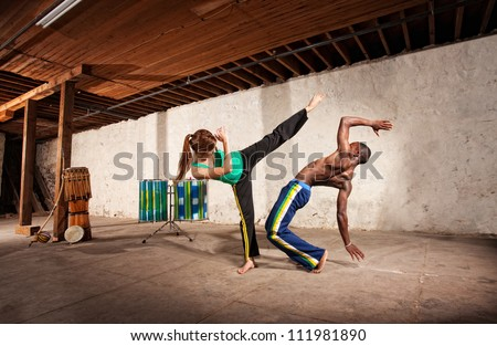 Young Black man dodging a Capoeria kick with berimbau player in back - stock photo