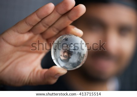 Young black man holding glass Earth model in hand. Concept for global connection, ecology or planet care. Macro close up, focus on globe  - stock photo