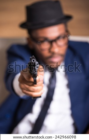 Young black man is wearing suit and hat with gun. Focus on gun.