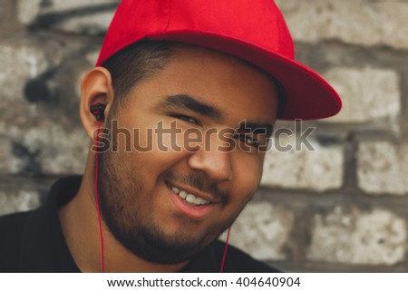 Young black man listening to the music in headphones with smile. Good music makes good mood - stock photo