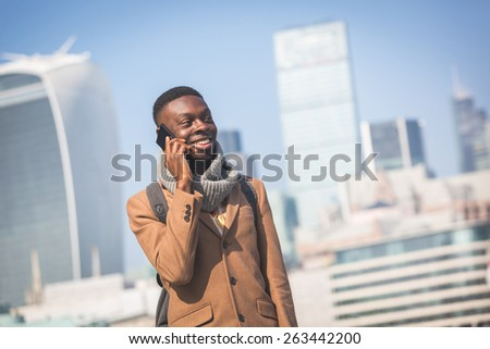 Young black man talking on mobile phone in London with city skyscrapers on background in a sunny day. He is wearing a coat and has a vintage backpack. - stock photo