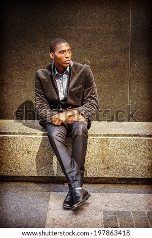 Young black man thinking outside. Dressing in a blazer, pants, leather shoes, a young black guy is sitting on a marble stone bench, looking up, waiting for you.  - stock photo