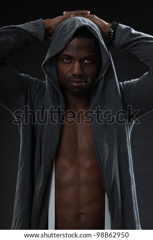 Young black man urban style looking tough isolated on dark background. Studio portrait.