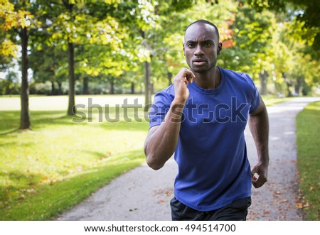 young black man wearing athletic wear running in the park