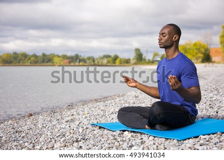 young black man wearing athletic wear sitting on the beach exercising yoga