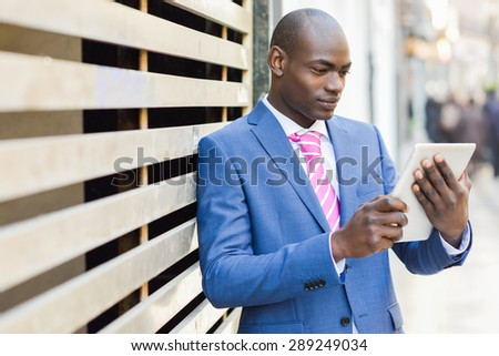 Young black man wearing blue suit looking at his tablet computer in the street. Young businessman in urban background - stock photo