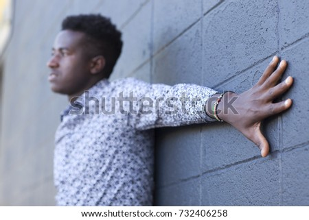 Young black man wearing Kenyan flag bracelet with arm outstretched on cement block wall with focus on bracelet