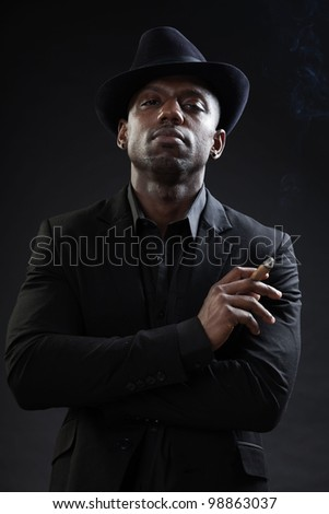Young black man wearing suit and hat gangster style smoking cigar isolated on dark background. Studio portrait.