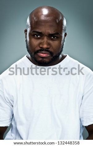 Young Black Man with Serious Expression over a Grey Background - stock photo
