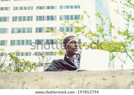 Young black man working outside. A young black college student is standing by the top of the wall outside an office building,  working on a computer. - stock photo