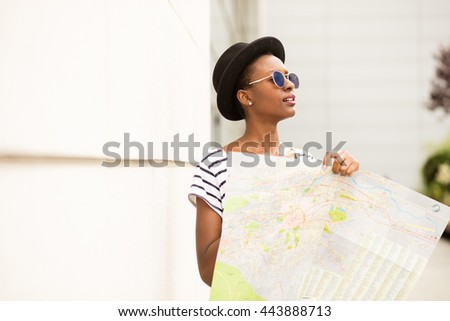 young black student traveling and checking the map outside the street