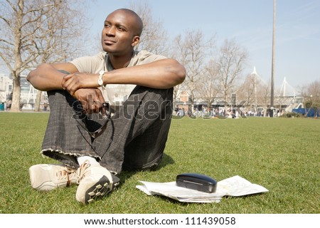 Young black tourist man sitting down on green grass in the city of London while visiting, smiling.