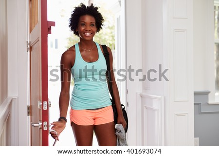 Young black woman arriving home after exercising - stock photo