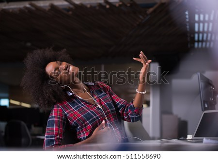 young black woman at her workplace in startup business office listening music on headphones and playing music instruments while relaxing
