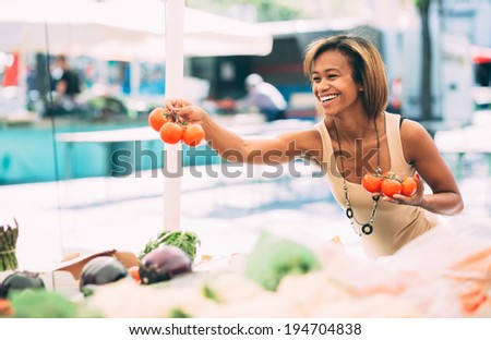 Young black woman buying vegetables at farmers market - stock photo