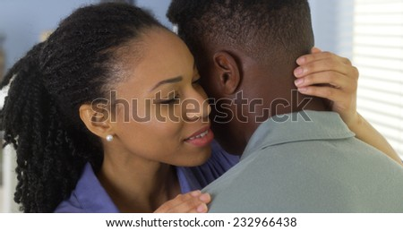 Young Black woman holding boyfriend and whispering to his ear - stock photo