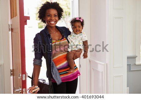 Young black woman holding child arriving home - stock photo