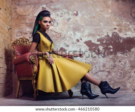 Young black woman in a gold dress sitting on a sofa