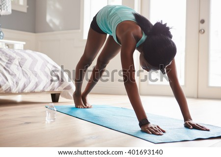 Young black woman in the downward-facing dog yoga pose - stock photo