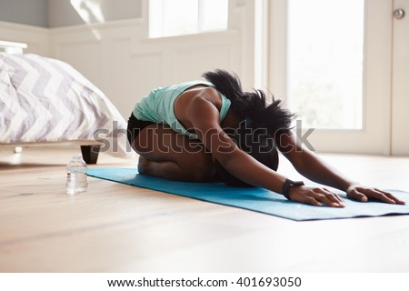 Young black woman practicing yoga in the cat stretch pose - stock photo