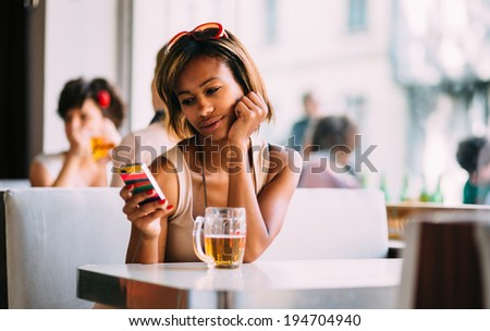 Young black woman texting and drinking beer in bar  - stock photo