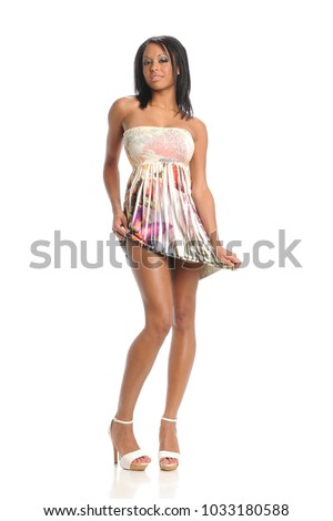 Young black woman wearing a flower dress posing isolated on a white background