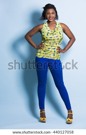 young black woman wearing casual outfit on light blue background - stock photo