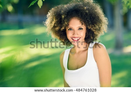 Young black woman with afro hairstyle smiling in urban park. Mixed girl wearing casual clothes.
