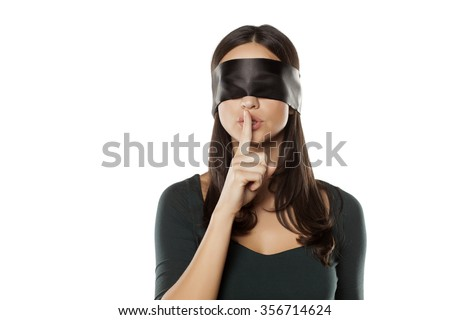 young blindfolded woman making a silent gesture - stock photo