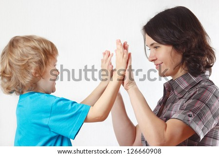 Young blond boy playing with his mother on a white background - stock photo