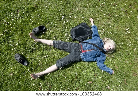 Young blond boy taking a breather on the lawn after school - stock photo