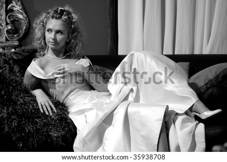 Young blond bride wearing white wedding dress  relaxing on sofa.