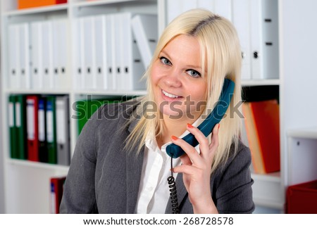 young blond businesswoman is calling in the office - stock photo