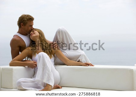 Young blond couple on white sofa. - stock photo