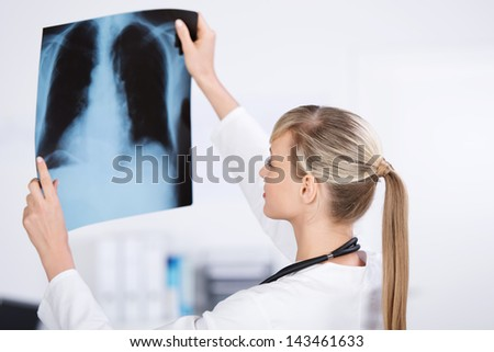 Young blond doctor checking the x-ray image