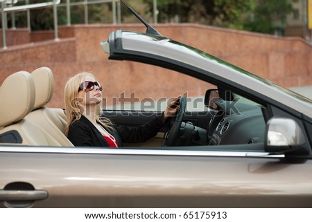 Young blond driving a convertible.