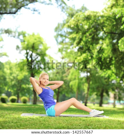 Young blond female exercising abs in a park, shot with a tilt and shift lens