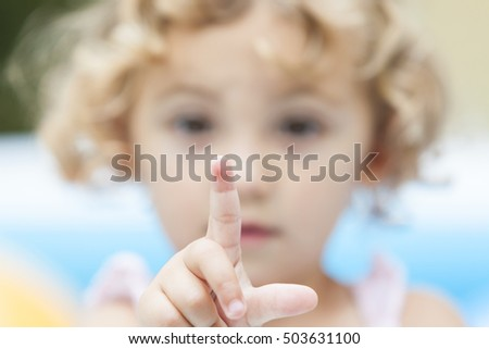 Young blond female girl child in front of swimming pool touching choosing or pointing on screen or camera with her finger