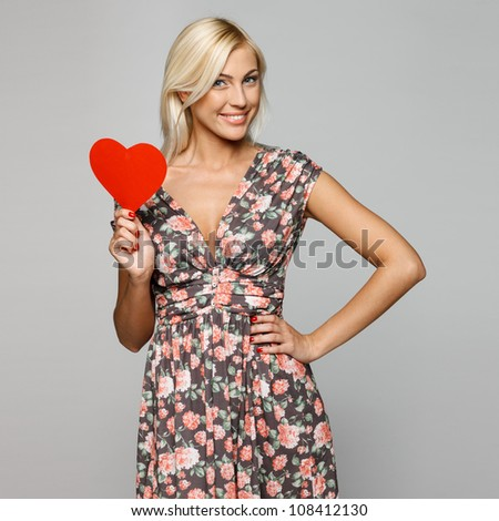 Young blond female in summer dress holding red heart shape isolated on gray background