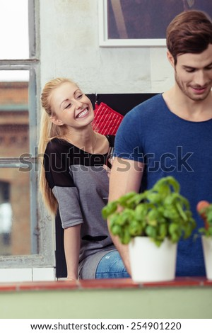 Young Blond Female Smiling Behind her Handsome Boyfriend Who is Busy Preparing for Something. - stock photo