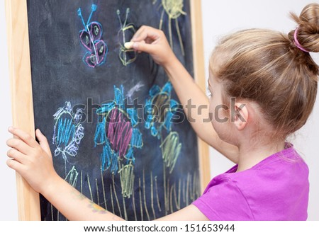 Young blond five years old caucasian girl drawing a picture with a chalk on blackboard - stock photo