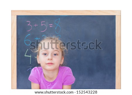 Young blond five years old caucasian girl in front of blackboard at school - isolated on white background - stock photo
