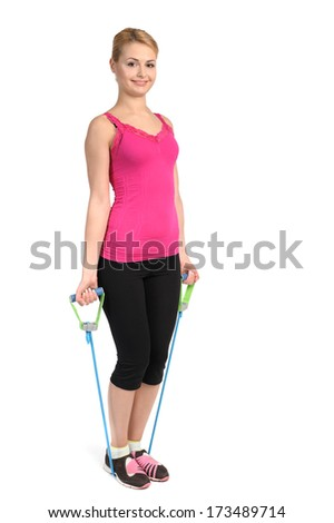 Young blond girl doing female biceps exercise using rubber resistance band. position 1 of 2. - stock photo
