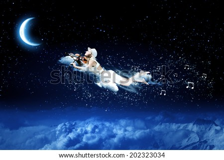 Young blond girl flying in night sky - stock photo