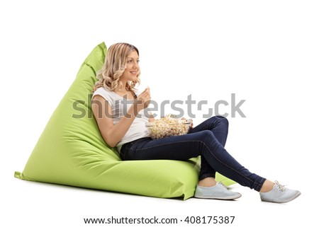 Young blond girl holding a bowl with popcorn seated on a green beanbag isolated on white background