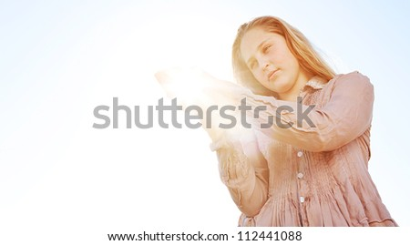 Young blond girl holding the sun in her hands, with sun rays filtering against a blue sky. - stock photo