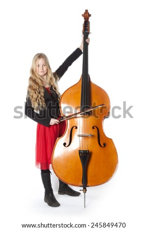 young blond girl in red dress plays double bass in studio against white background - stock photo